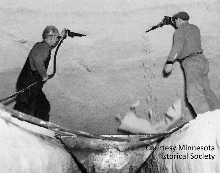 Workers used air guns to blast the silica sand out of the many tunnels that had been excavated 100 feet beneath the Ford plant. The sand was loaded into small electric carts and carried by conveyer up to the furnaces where it would be made into glass. Courtesy Minnesota Historical Society