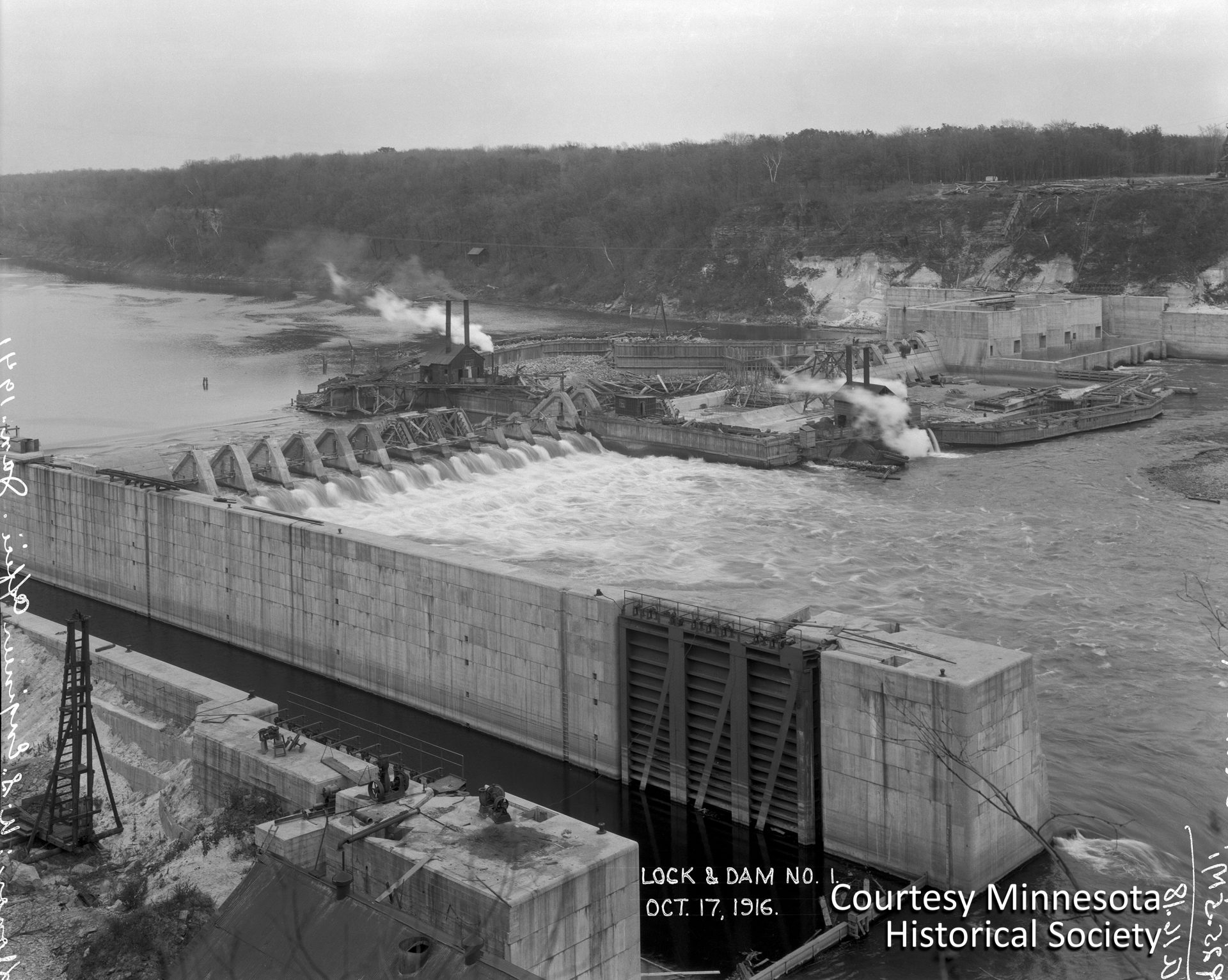 This 1916 photo, taken from the west side of the river, shows Lock & Dam No. 1 under construction. At the upper right are the original foundations built by the Army Corps of Engineers for a future hydroelectric plant. Those foundations would later be demolished to make way for Henry Ford's larger turbine generators. Courtesy Minnesota Historical Society