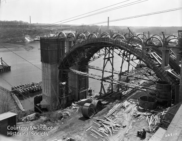 The Intercity Bridge, seen under construction in this 1926 photo, was one of the few bridges spanning the Mississippi that connected Minneapolis and Saint Paul. The Twin Cities Assembly Plant can be seen in the background. Courtesy Minnesota Historical Society